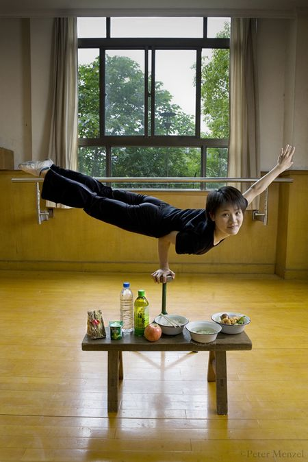 Cao Xiaoli, a professional acrobat, balances on one hand with her day's worth of food at Shanghai Circus World in Shanghai, China. (From the book What I Eat: Around the World in 80 Diets.) The caloric value of her day's worth of food on a typical day in June was 1700 kcals. She is 16 years of age; 5 feet 2 inches tall; and 99 pounds. Cao Xiaoli lives in a room with nine other girls. She started her career as a child, performing with a regional troupe in her home province of Anhui. Now she practices five hours a day, attends school with the other members of her troupe, and performs seven days a week. She says what she likes best about being an acrobat is the crowd's reaction when she does something seemingly dangerous.